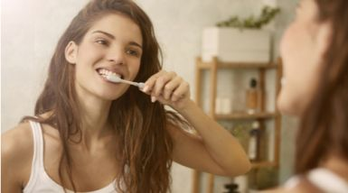 A young woman brushes her teeth, watching her reflection in the mirror. >   <br clear=