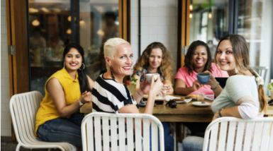 A group of women of different ages sit around a large table, drinking coffees and smiling at the camera.