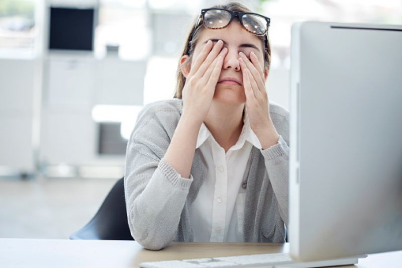 Woman rubbing her eyes in front of laptop out of tiredness