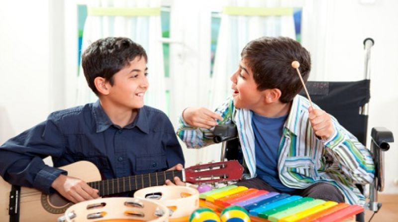 Two boys play music instruments