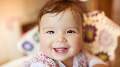 A smiling baby girl with four teeth stands in her crib