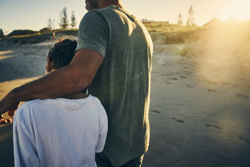 Father and son walk together on a beach
