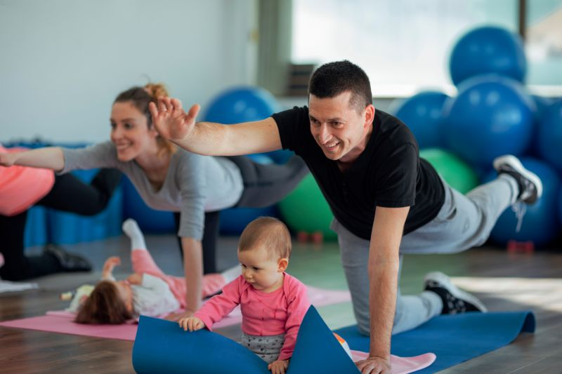A dad does a yoga class with his baby playing beneath him on the mat.