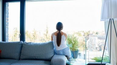 A woman sits on her couch and looks out the window.