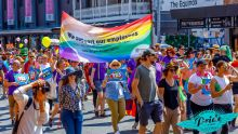 A group of Queensland Health employees walk in the Brisbane Pride March behind a Queensland Health rainbow banner.