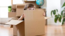 A little girl sits in a moving box, peering out over the top cheekily.