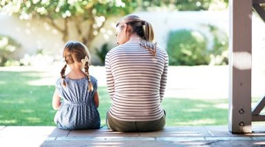 A mother and her young daughter sit on the back veranda talking, backs to the camera.