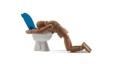 wooden mannequin hugging toilet bowl indicating they're vomiting