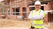A male tradesperson stands on a building site, arms crossed, smiling.