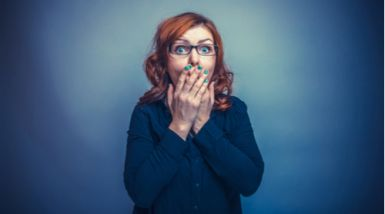A lady covers her mouth after being surprised by a hiccup.