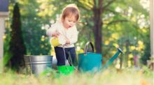 A toddler stands outside over two buckets and a watering can, she pours water from a smaller bucket into one of the larger buckets.