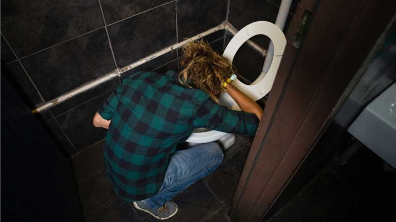 young man holding back his hair while vomiting into a toilet in pub