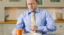 A man sits at a dinner table after eating. He holds his fist against his upper abdomen and has a painful expression.