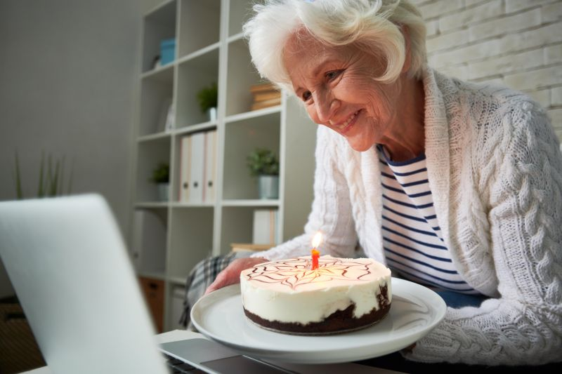 An older woman holds a birthday cake up to a laptop for a video chat.