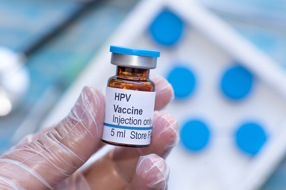 A latex gloved hand holds a vial of HPV vaccine