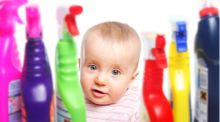 A toddler sits behind a shelf of cleaning products, she looks like she will pick one up.