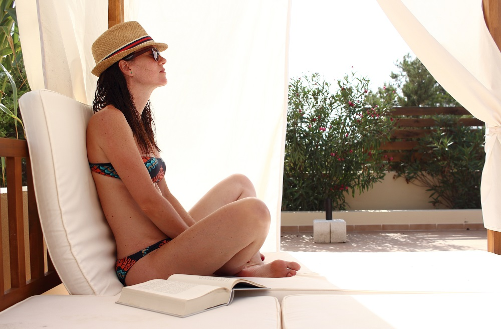 A woman sits on a pool chair in her swimming togs, book resting beside her.