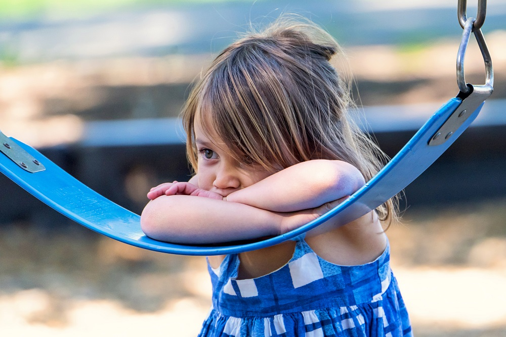 A small girl rests her arms and face on the base of a swing, looking sad.