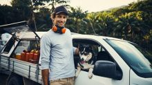 A smiling man stands next to his work ute, safety ear muffs around his neck, his dog peering out the window.
