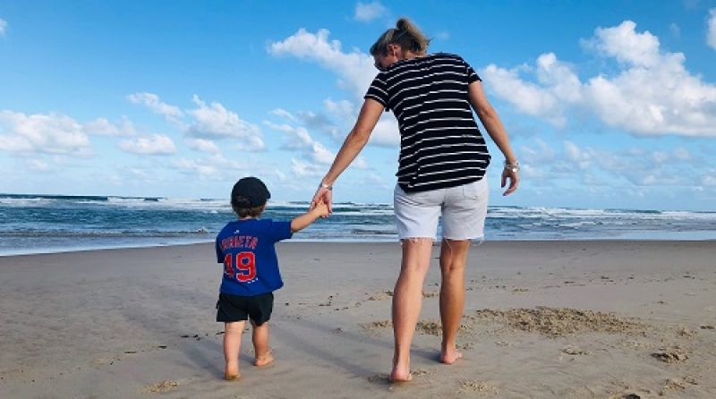 Boy and his mother walking on the beach