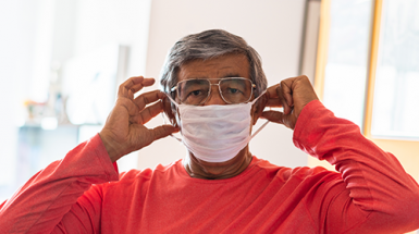 A man fits his facemask over his hears to protect himself from COVID-19