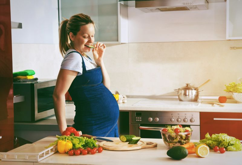 A pregnant woman cooks in the kitchen, the bench filled with vegetables. She chews on a slice of cucumber.