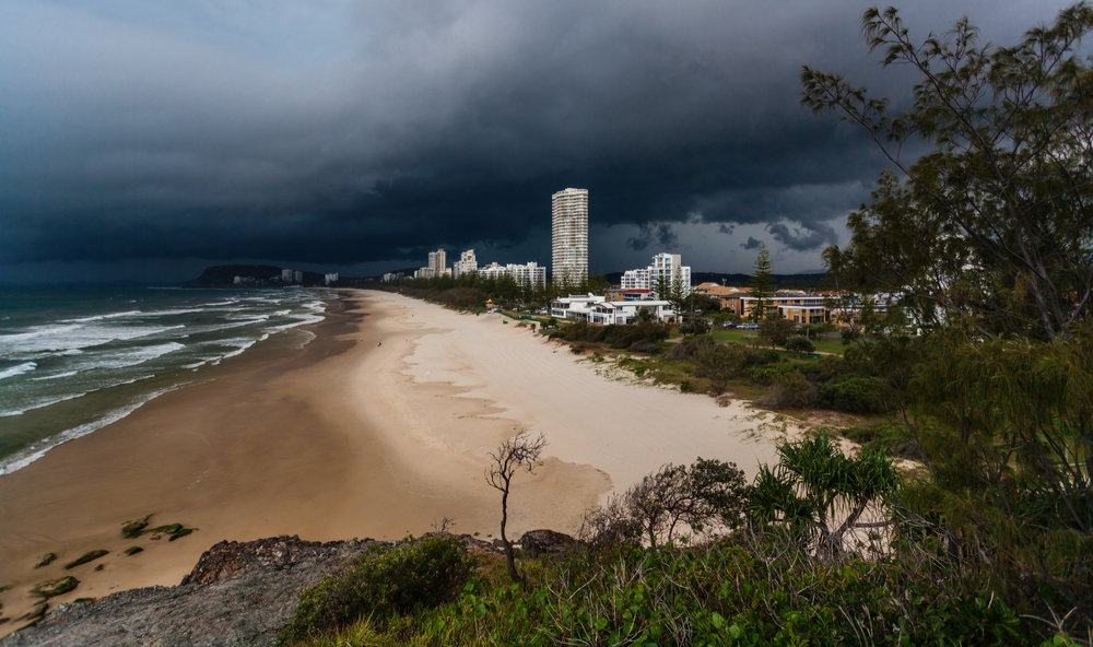 Dark storm clouds roll in over a Queensland beach.