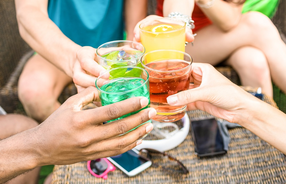 People sit in a circle outside, we see their hands reaching in to the centre with cups of colourful liquids to cheers.