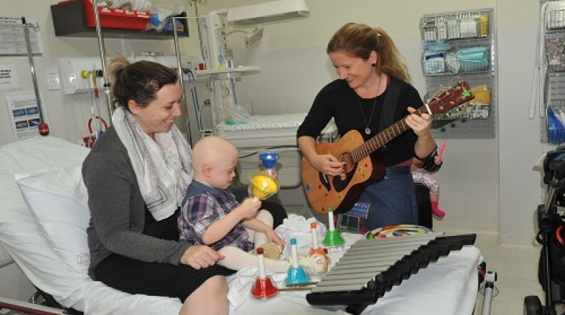 A music therapist plays guitar for a child and another woman in hospital