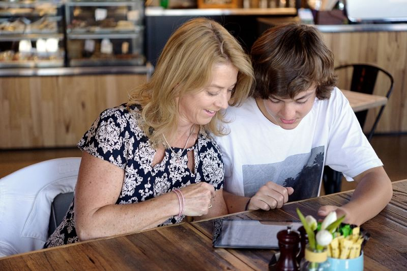 A mum and son sit at the kitchen table looking at a tablet.