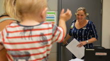 A toddler waves to a dietitian as she enters the room