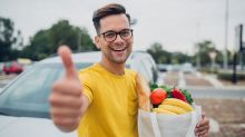 A man hold a bag of groceries in front of his car and gives a thumbs up.