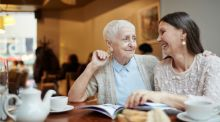 Two older women sit in a cafe, one has her hand on the other's shoulder, reassuring her.