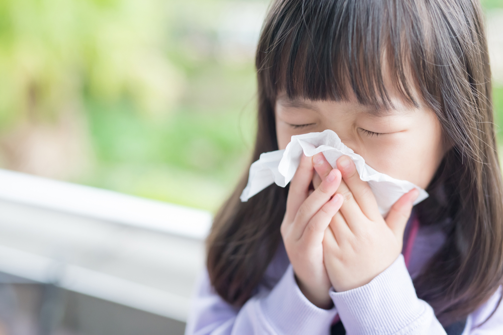 A young Asian girl blows her nose into a tissue.
