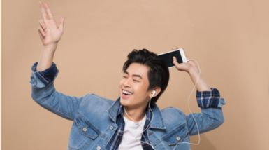 A young Asian man dances while listening to music through headphones.