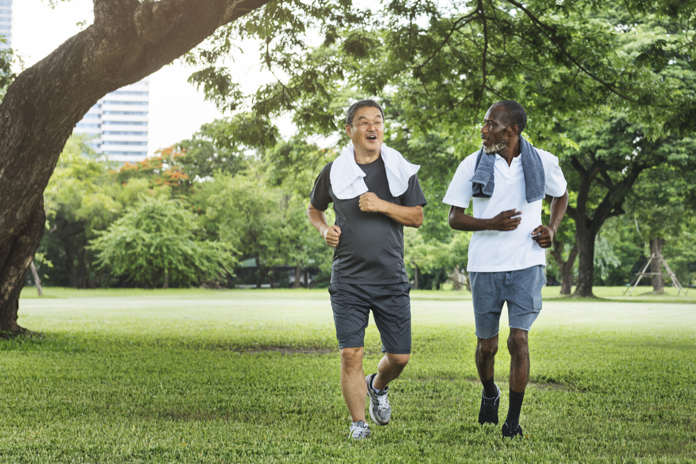 Two older men walk through a park after exercising.