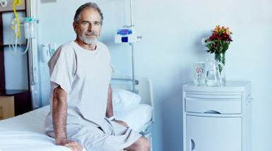 A man sits on the edge of his hospital bed wearing a hospital gown.