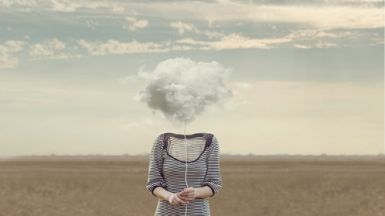 A woman standing in a field, a storm cloud floating where her face would be.