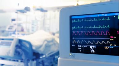 A picture of a heart rate monitor in front of an ICU bed.