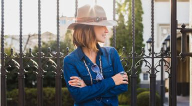 On a sunny day, a woman stands wearing a hat, sunglasses and a long sleeve shirt.