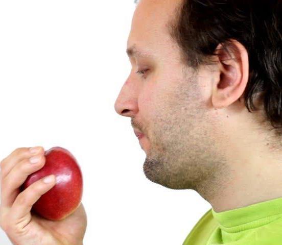 A man preparing to eat an apple