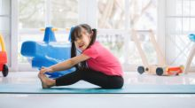 A little girls sits on the floor stretching her legs and grimacing.