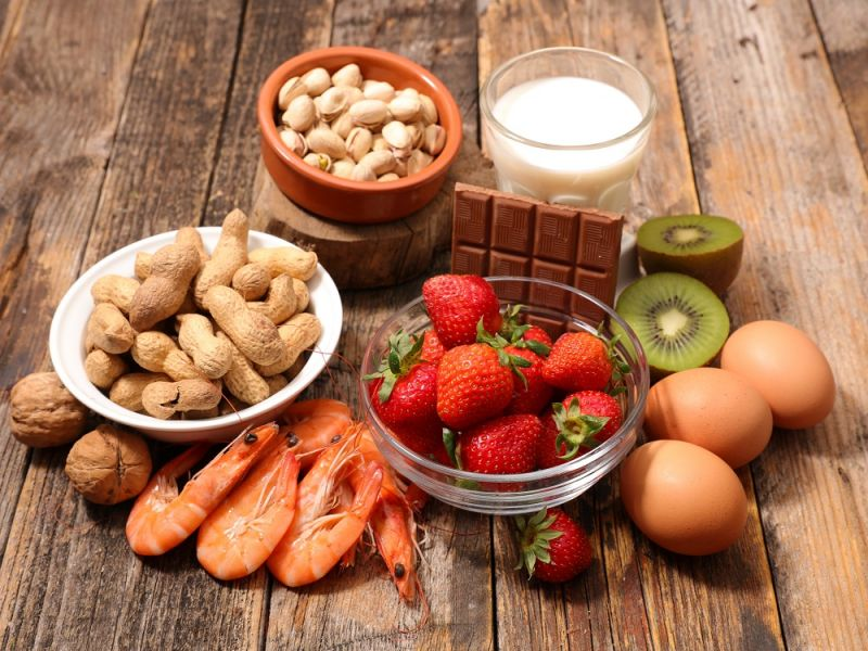 An array of foods that are common allergens sit on a table, including strawberries, nuts, grains, eggs, prawns and chocolate.