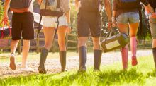 A group of people in gumboots walk into a music festival, lit by afternoon sun.