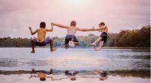 Three young boys run and jump into a placid lake at dusk.