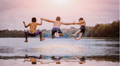 Three young boys run and jump into a placid lake at dusk.