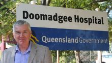 Dr John Currie stands in front of the sign for Doomadgee Hospital