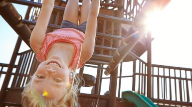 Girl hangs upside down from monkey bars and smiles.