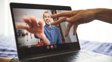 A man on a video call reaches out his hand to touch the screen.