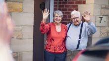 A older couple stand at their front door, waving to someone in a car.